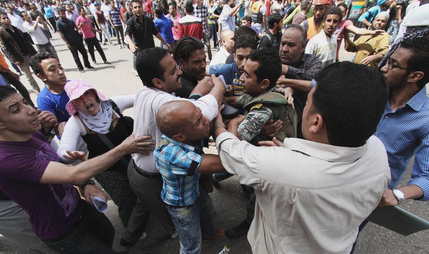 Protesters clash with an Egyptian soldier outside the Defense Ministry in Cairo on Wednesday, May 2, 2012. (AP Photo)
