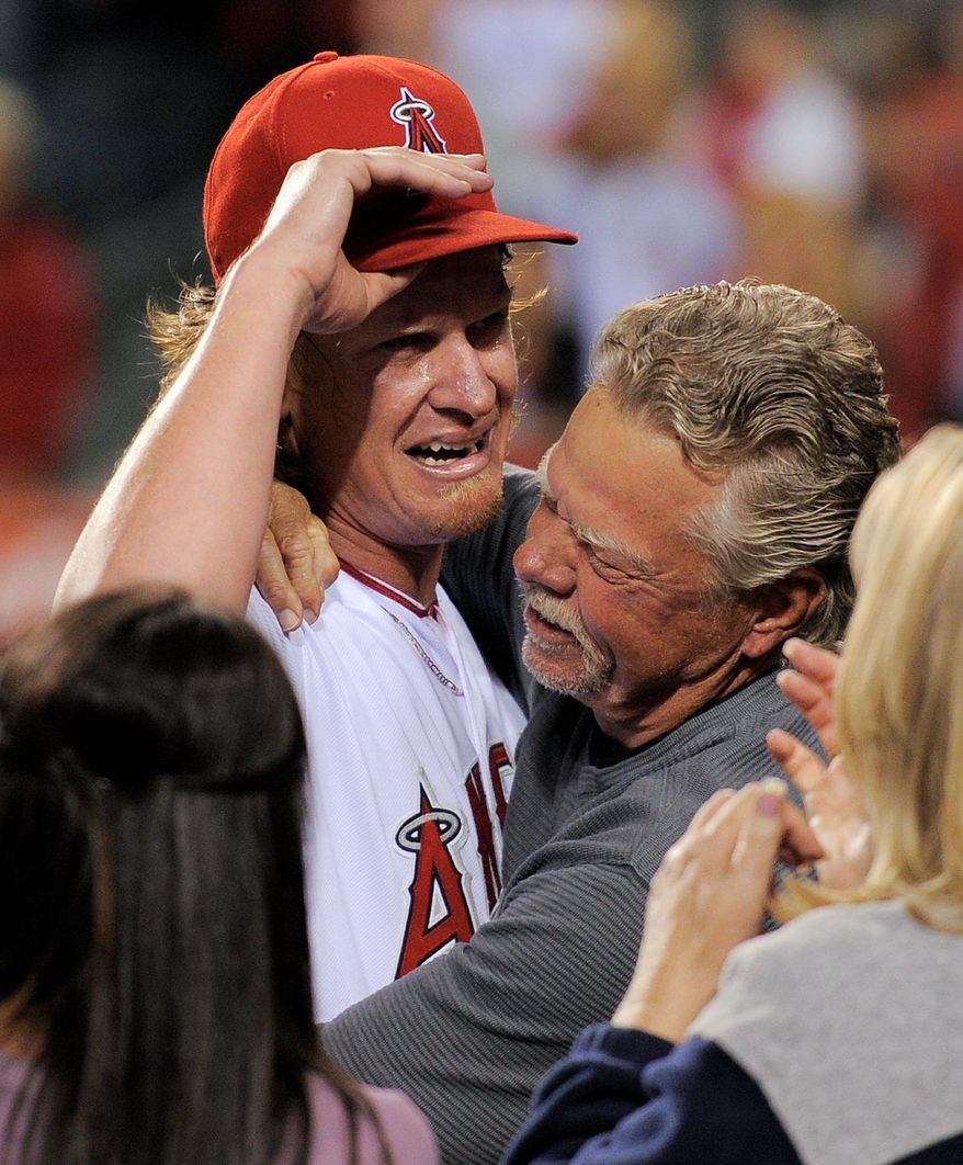 A tearful Jered Weaver is hugged by his father, Dave, after pitching his first no-hitter and the 10th in Angels history Wednesday night. (Associated Press)