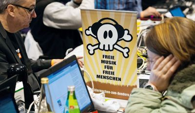 """Members of Germany's Pirate Party with a poster reading """"Free Music for Free People"""" appeals to young voters as an anti-establishment movement. It is polling at 14 percent of the national vote. (Associated Press)"""