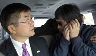 Blind activist lawyer Chen Guangcheng (right), accompanied by Gary Locke, U.S. ambassador to China, makes a phone call on the way to a hospital in Beijing on Wednesday, May 2, 2012. (AP Photo/U.S. Embassy Beijing Press Office)