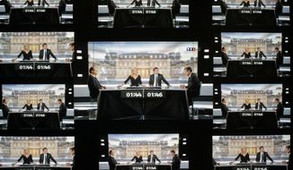 A wall screen shows the televised debate between Francois Hollande, Socialist Party candidate for the presidential election and Nicolas Sarkozy, current president and conservative rival for re-election, at the TF1 television studio in Boulogne-Billancourt, outside Paris on May 2, 2012. (Associated Press)