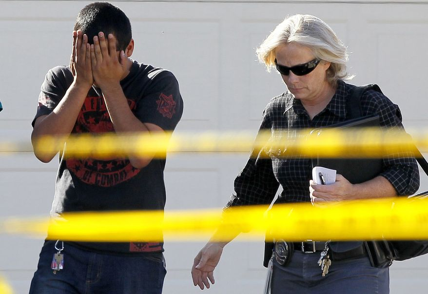 A police officer walks May 2, 2012, with a man who said he had a child inside of the home where five people were shot and killed in Gilbert, Ariz. Police identified one of the five people killed as a former Marine with ties to neo-Nazi and Minutemen groups. (Associated Press)