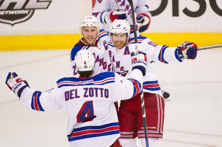 New York Rangers right wing Ryan Callahan (24), top left, celebrates his goal on Washington Capitals goalie Braden Holtby (70) with teammates New York Rangers defenseman Michael Del Zotto (4), bottom, and New York Rangers center Brad Richards (19) to put the New York Rangers up 1-0 in the second period as the Washington Capitals take on the New York Rangers in playoff NHL hockey at the Verizon Center, Washington, D.C., Wednesday, May 2, 2012. (Andrew Harnik/The Washington Times)
