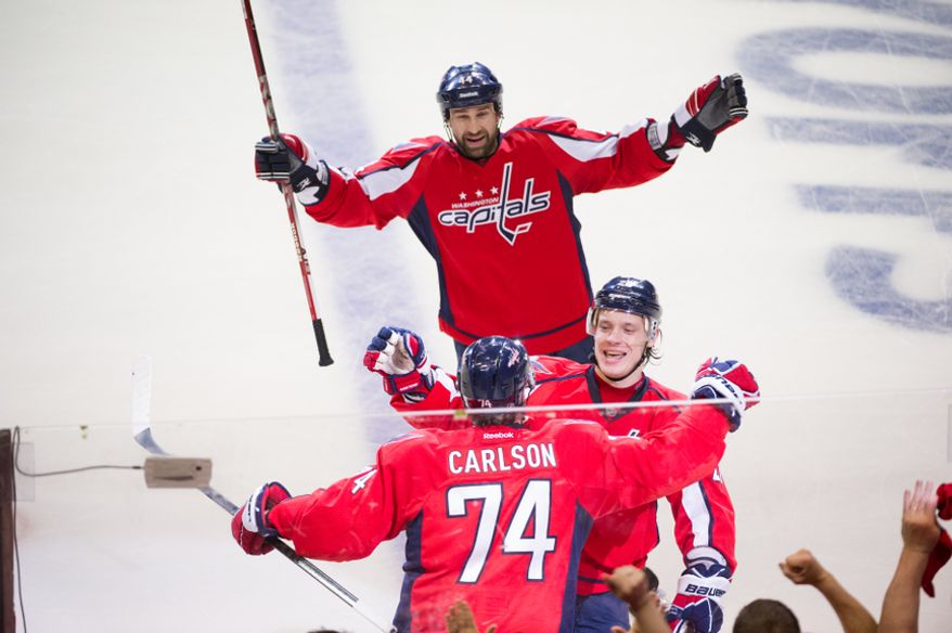 Washington Capitals defenseman John Carlson (74), bottom left, celebrates his goal on New York Rangers goalie Henrik Lundqvist (30) with his teammates Washington Capitals defenseman Roman Hamrlik (44), top center, and Washington Capitals left wing Alexander Semin (28), bottom right, to even the score 1-1 in the second period as the Washington Capitals take on the New York Rangers in playoff NHL hockey at the Verizon Center, Washington, D.C., Wednesday, May 2, 2012. (Andrew Harnik/The Washington Times)