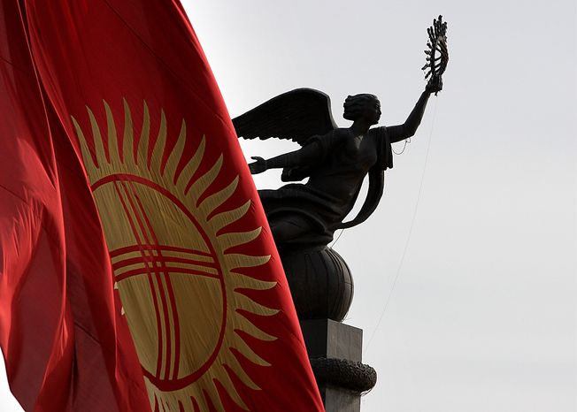 **FILE** The Kyrgyz national flag flies at half staff April 9, 2010, in front of the statue of independence on a central square in Bishkek, Kyrgyzstan. (Associated Press)