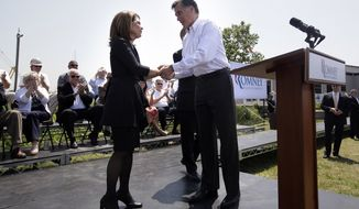Republican presidential candidate and former Massachusetts Gov. Mitt Romney holds the hands of Rep. Michele Bachmann, Minnesota Republican, on May 3, 2012, at a campaign stop in Portsmouth, Va. (Associated Press)