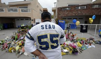 "San Diego Chargers fan Jerry Lopez looks over a memorial set-up in the driveway of the house of former NFL star Junior Seau on May 3, 2012, in Oceanside, Calif. Seau's apparent suicide the previous day stunned an entire city and saddened former teammates who recalled the former NFL star's ferocious tackles and habit of calling everybody around him ""Buddy."" (Associated Press)"