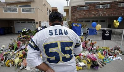 """San Diego Chargers fan Jerry Lopez looks over a memorial set-up in the driveway of the house of former NFL star Junior Seau on May 3, 2012, in Oceanside, Calif. Seau's apparent suicide the previous day stunned an entire city and saddened former teammates who recalled the former NFL star's ferocious tackles and habit of calling everybody around him """"Buddy."""" (Associated Press)"""