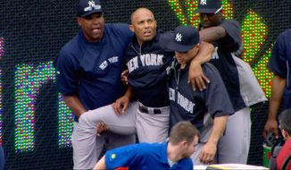 In this image taken from video, New York Yankees manager Joe Girardi, right, helps Mariano Rivera, top center, after Rivera tore his ACL shagging fly balls during batting practice before a game with the Kansas City Royals, Thursday, May 3, 2012, in Kansas City, Mo. The Yankees closer was carted off the field and sent for further tests. (AP Photo/YES Network)