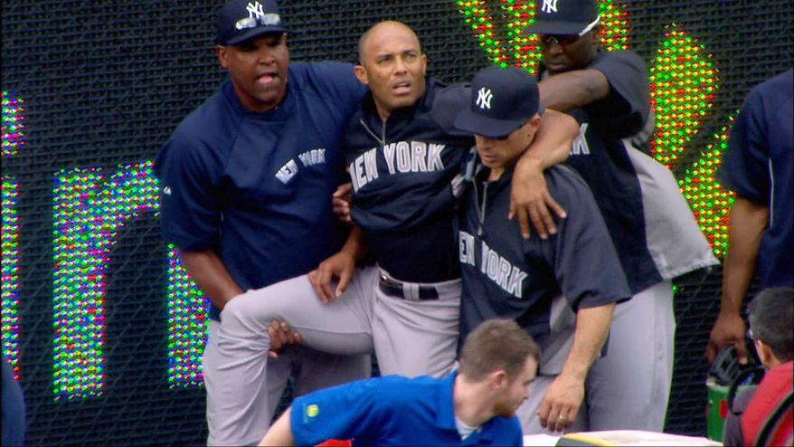 In this image taken from video, New York Yankees manager Joe Girardi, right, helps Mariano Rivera, top center, after Rivera twisted his right knee shagging fly balls during batting practice before a baseball game with the Kansas City Royals, Thursday, May 3, 2012, in Kansas City, Mo. The Yankees closer was carted off the field and sent for further tests. (AP Photo/YES Network)