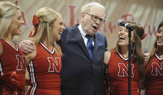 Warren Buffett, chairman and CEO of Berkshire Hathaway, sings with University of Nebraska cheerleaders prior to the annual shareholders meeting in Omaha, Neb., Saturday, May 5, 2012. Berkshire Hathaway is holding it's annual shareholders meeting this weekend. (AP Photo/Dave Weaver)