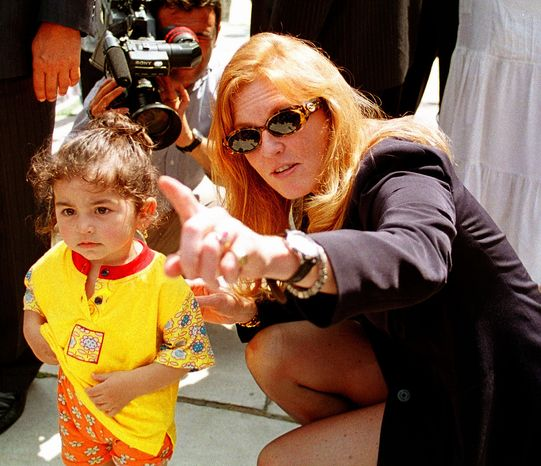 ** FILE ** In this Thursday, June 11, 1998, file photo Britain's Duchess of York Sarah Ferguson points at the cameras as she kneels beside a Turkish child during her visit to the Blue Mosque in Istanbul. (AP Photo/Murad Sezer, File)