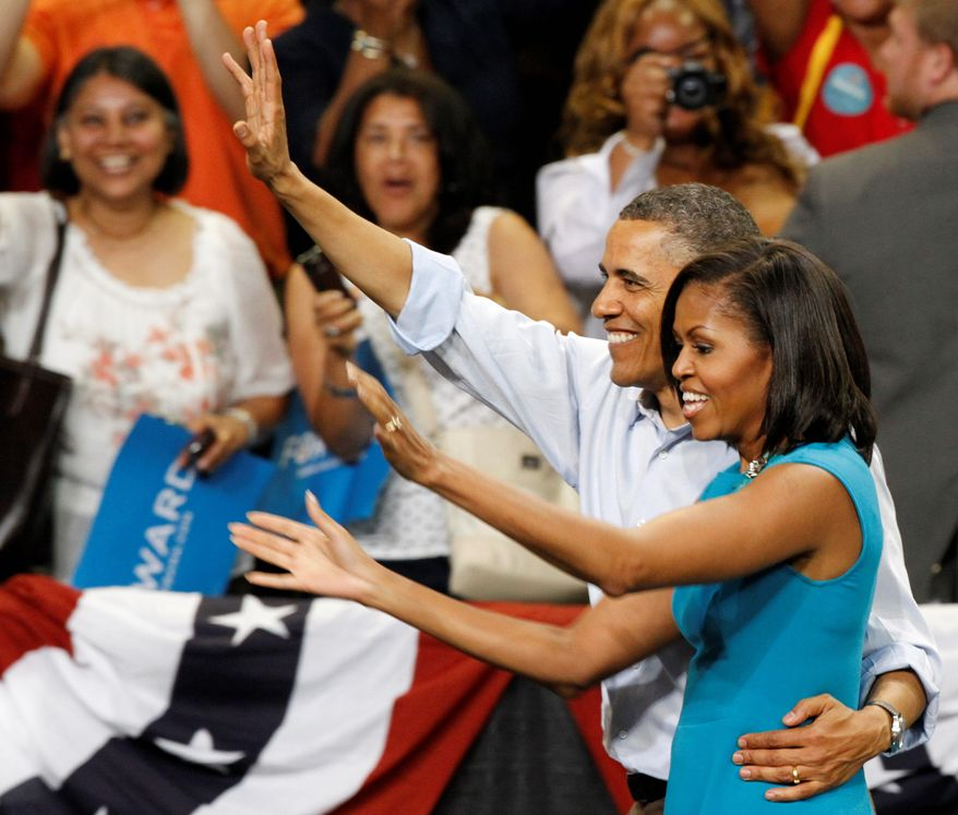 """President Obama and his wife, Michelle, acknowledge the crowd Saturday during a campaign rally at Virginia Commonwealth University in Richmond. His speech was interrupted several times with chants of """"four more years."""" (Associated Press)"""