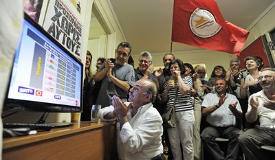 Members of the Coalition of the Radical Left enthusiastically watch election results showing their party win enough to possibly become the new No. 2 party in the parliament. (Associated Press)