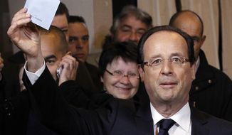Socialist Party presidential candidate Francois Hollande shows his ballot before voting in the second round of the French presidential election in Tulle, France, on Sunday, May 6, 2012. (AP Photo/Christophe Ena)