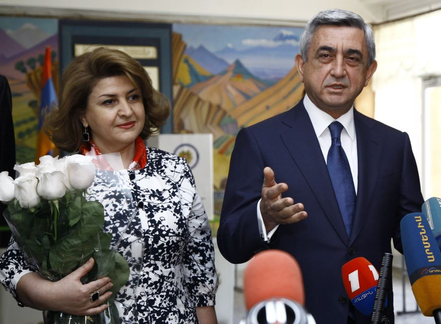 Armenian President Serge Sarkisian, who also is Republican Party president, speaks to the press after he voted during parliamentary elections in Yerevan, Armenia, on Sunday, May 6, 2012. Rita Sarkisian, the president's wife, smiles at left. (AP Photo/PanArmenian, Tigran Mehrabyan)