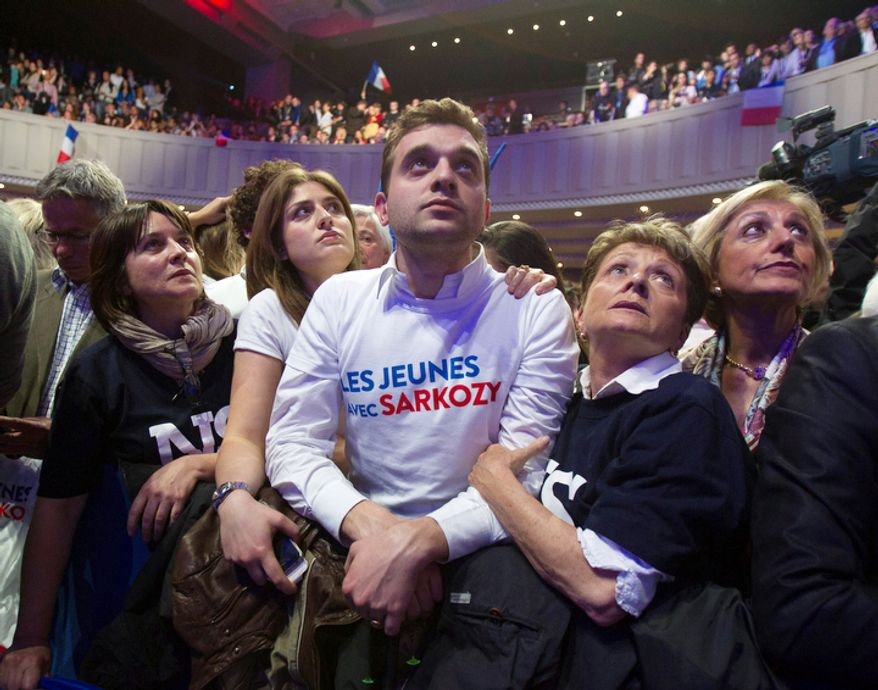 """Supporters of outgoing French President Nicolas Sarkozy's Union for a Popular Movement (UMP) with a T-shirt reading """"Youth for Sarkozy"""". (AP Photo/Michel Euler)"""
