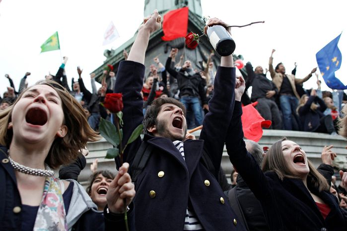 Supporters of Socialist Party candidate for the presidential election Francois Hollande react after the first results of the second round of French presidential elections were announced at Bastille Square in Paris.  (AP Photo/Laurent Cipriani)