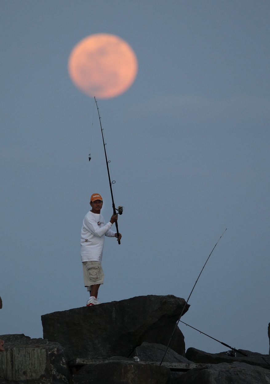 """A fisherman casts a line from a jetty as the """"supermoon"""" appears over the Atlantic Ocean on Saturday, May 5, 2012, near Bal Harbour, Fla. (AP Photo/Wilfredo Lee)"""
