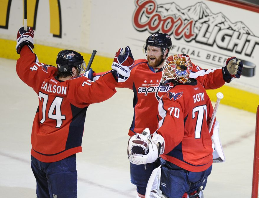 Washington Capitals goalie Braden Holtby (70) celebrates a  3-2 win over the New York Rangers with Karl Alzner, center, and John Carlson, after Game 4 of a second-round NHL Stanley Cup playoff series, Saturday, May 5, 2012, in Washington. (AP Photo/Nick Wass)
