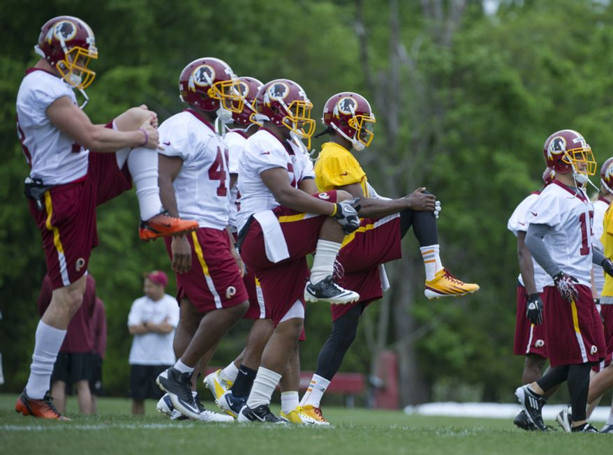 Redskins players, including newly drafted quarterback Robert Griffin III, right, in yellow, do stretching drills across the field. (Barbara L. Salisbury/The Washington Times)