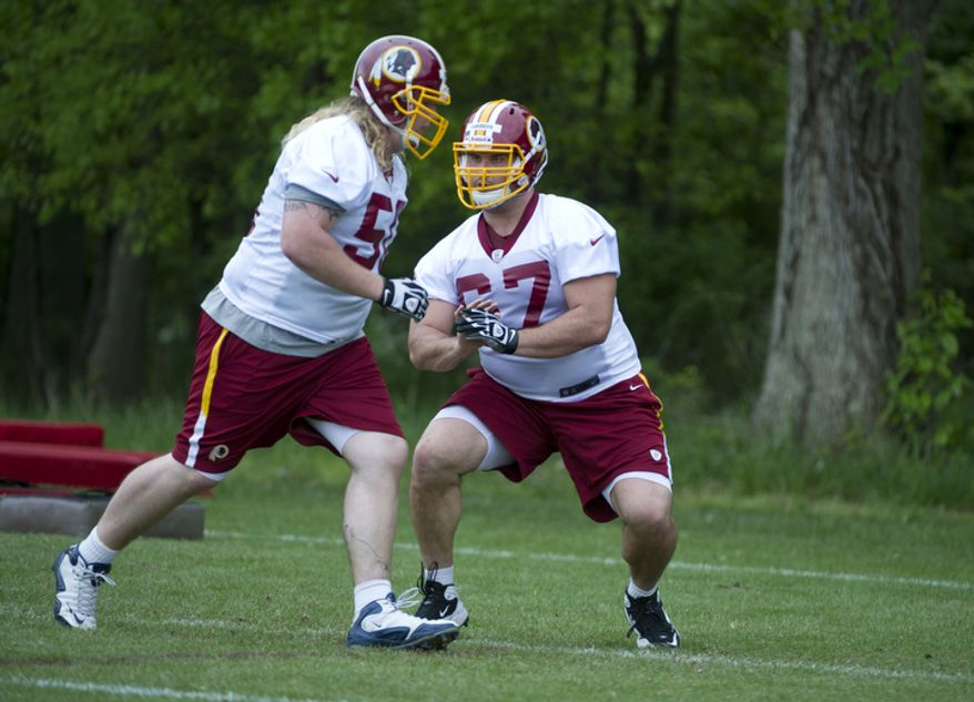 Josh LeRibeus, right, an offensive guard drafted from SMU, goes through blocking drills at Redskins Park. (Barbara L. Salisbury/The Washington Times)