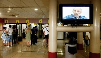 Passengers line up to check with customs officials before departing in 2010 from Jose Marti International Airport in Havana. A TV screen shows Cuba's revoluntionary leader Fidel Castro during an interview. Cuba's communist government is rumored to be on the verge of a momentous decision to end a half-century of travel restrictions. (Associated Press)
