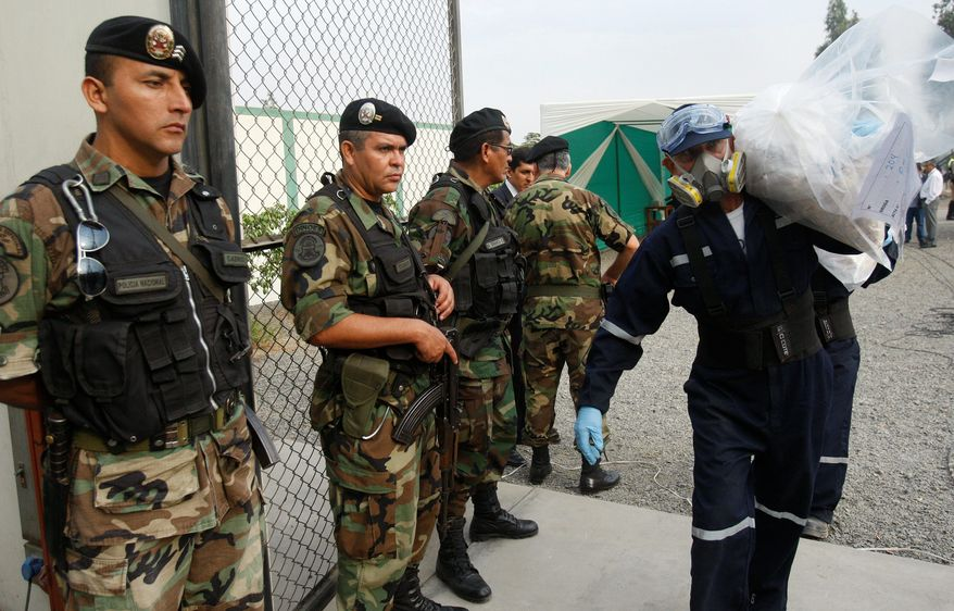 A city employee carries a bag of cocaine to an incinerator at a police base in Lima, Peru, a small part of the more than 4 tons of drugs seized in March and April - including cocaine, marijuana and heroin - that were burned there. Increased drug trafficking in Peru has been driven, in part, by the success of a U.S.-backed operation last decade that pushed operations out of Colombia into its neighbor to the south. Now, the U.S. is helping the Peruvian government fight the same battles. (Associated Press)