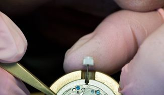 A watchmaker for Nomos assembles a watch in Glashutte, Germany. At least 50 percent of the timekeeping movement must be made here by hand. The watches sell from $1,315 to $5,000. (Christian Burkert/Special to The Washington Times)