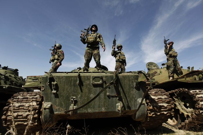 ** FILE ** During a training session at Camp Morehead on the outskirts of Kabul, Afghanistan, in March 2011, Afghan National Special Force soldiers stand on tanks that were destroyed in the Soviet occupation and civil war. (AP Photo/Dar Yasin, File)