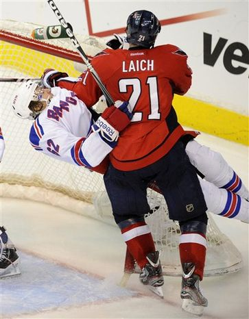 Washington Capitals center Brooks Laich (21) and New York Rangers left wing Carl Hagelin (62), of Sweden, crash into the net during the second period of Game 4 of an NHL hockey Stanley Cup second-round playoff series, Saturday, May 5, 2012, in Washington. (AP Photo/Nick Wass)