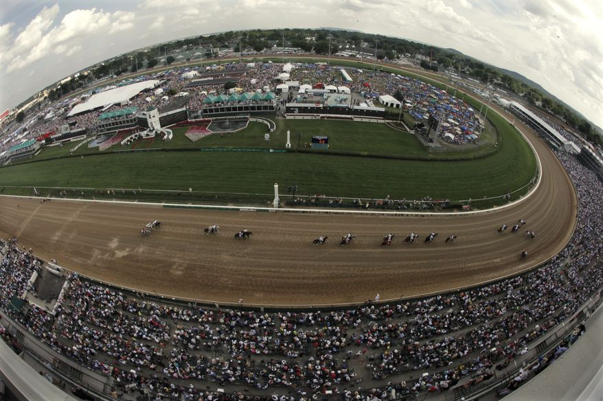 In a photo taken with a fisheye lens, jockeys and their horses make their way past the grand stand at the Churchill Downs before the 10th race at 138th Kentucky Derby horse race on May 5, 2012, in Louisville, Ky. (Associated Press)