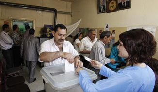 A Syrian casts his vote at a polling station in Damascus, Syria, the capital, during parliamentary elections on Monday, May 7, 2012. (AP Photo/Muzaffar Salman)