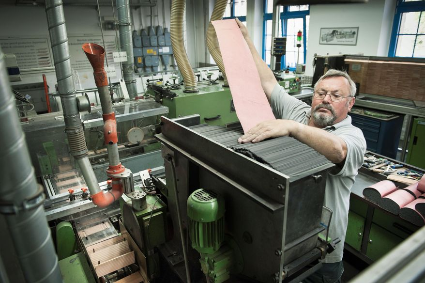 An employee restocks a machine with lead at the Faber-Castell pencil factory in Stein, Germany. Treating workers well has paid dividends for the company, the firm's owner said. (Christian Burkert/Special to The Washington Times)
