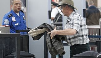 A traveler passes April 30, 2012, through a security check point at Portland International Airport, in Portland, Ore. (Associated Press)