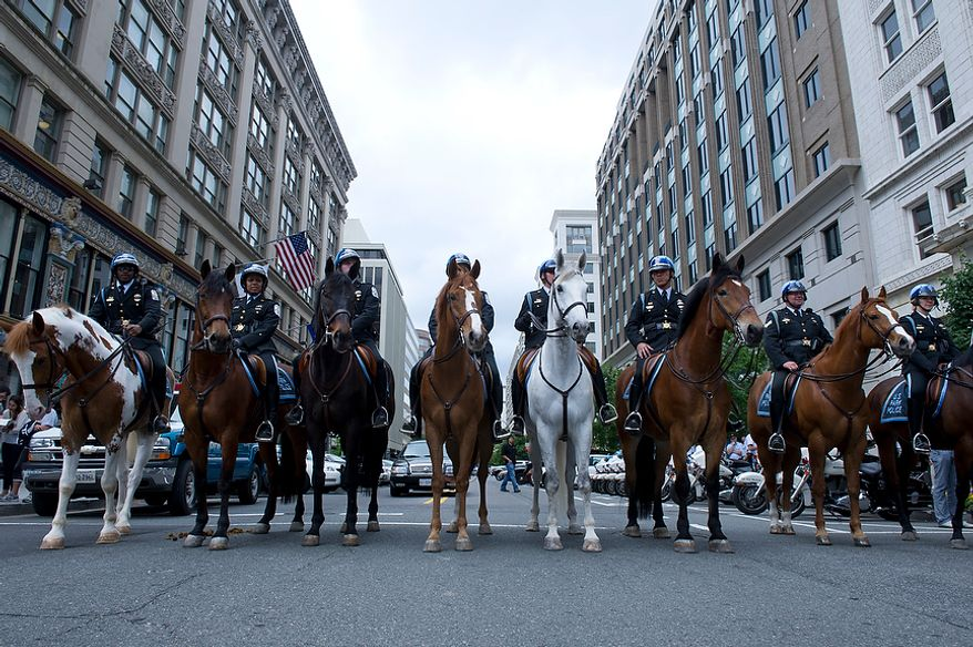 Horse-mounted U.S. Park Police officers stand across G Street Northwest to block off the street in honor of the annual Blue Mass honoring law enforcement and public safety officials Tuesday, May 8, 2012 at St. Patrick's in the City in Northwest Washington, D.C. (Barbara L. Salisbury/The Washington Times)