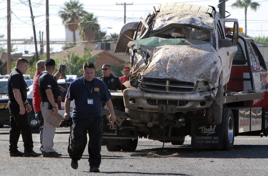 Investigators look over a vehicle that crashed and rolled following a pursuit by U.S. Border Patrol agents early on Wednesday, May 2, 2012, in Casa Grande, Ariz. (AP Photo/Casa Grande Dispatch, Steven King)