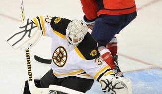 Boston Bruins goalie Tim Thomas (30) moves to the puck against Washington Capitals left wing Matt Hendricks (26) during the second period of Game 6 of an NHL hockey Stanley Cup first-round playoff series, Sunday, April 22, 2012, in Washington. (AP Photo/Nick Wass)
