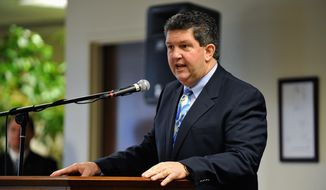 Postmaster General Patrick R. Donahoe speaks at the Helena, Mont., airport last month. After visiting rural areas, Mr. Donohoe has proposed cutting hours at some rural post offices or finding other options to keep at least some open. (Associated Press)