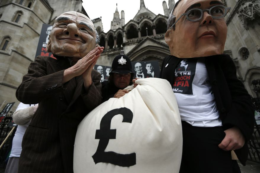 Protesters dressed up as Rupert Murdoch (left) and his son James pose April 24, 2012, for photographers as they demonstrate outside the High Court in London. Rupert Murdoch was testifying during Lord Justice Brian Leveson's inquiry into media ethics to answer questions about Murdoch's role in the phone hacking scandal at his now-defunct News of the World tabloid. (Associated Press)