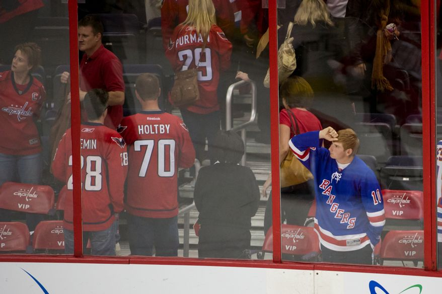 A dejected New York Rangers fan looks out onto the ice after the Washington Capitals hold on to defeat the New York Rangers 2-1 in game six of the NHL eastern conference playoffs semifinals at the Verizon Center, Washington, D.C., Wednesday, May 9, 2012 (Andrew Harnik/The Washington Times)