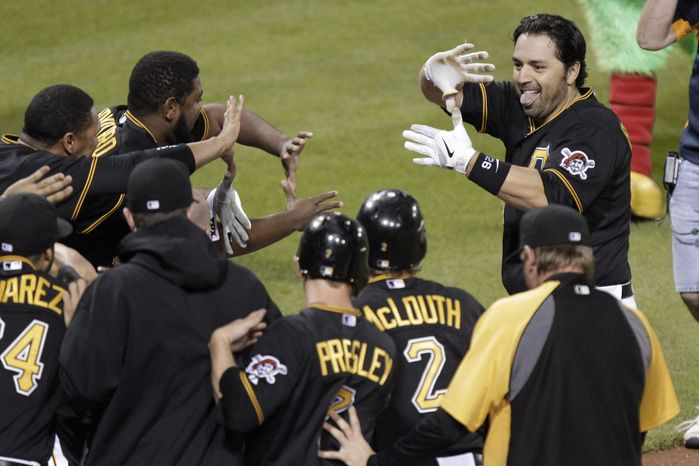 Pittsburgh Pirates' Rod Barajas, top right, is greeted by teammates after hitting a two-run home run off Washington Nationals pitcher Henry Rodriguez in the ninth inning in Pittsburgh on Tuesday, May 8, 2012. The Pirates won 5-4 in the walk-off homer. (AP Photo/Gene J. Puskar)