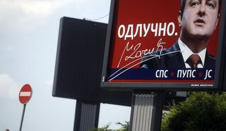 A man passes by an election billboard in central Belgrade, Serbia, that depicts Ivica Dacic, the leader of the Socialist Party of Serbia, formed by late strongman Slobodan Milosevic, on May 5, 2012. (Associated Press)