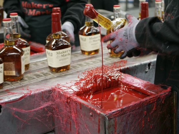 A bottle of Maker's Mark bourbon is dipped in red wax at the company's distillery in Loretto, Ky., in April 2009.  (AP Photo/Ed Reinke)