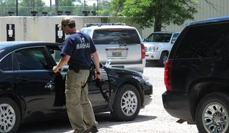 A U.S. Marshal stands next to his car holding a rifle in the parking lot of a command center set up to coordinate the search for two Tennessee girls and the man accused of abducting them and killing their mother and sister on Thursday May 10, 2012, in Guntown, Miss. The hunt for Adam Mayes and the two young sisters he is accused of kidnapping has encompassed parts of at least three counties in northern Mississippi. (AP Photo/Adrian Sainz)