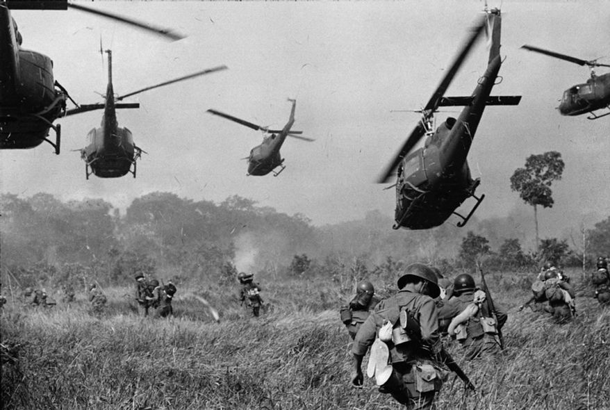In this March 1965 file photo shot by Associated Press photographer Horst Faas, hovering U.S. Army helicopters pour machine gun fire into the tree line to cover the advance of South Vietnamese ground troops in an attack on a Viet Cong camp 18 miles north of Tay Ninh, Vietnam, northwest of Saigon near the Cambodian border.  (AP Photo/Horst Faas, File)