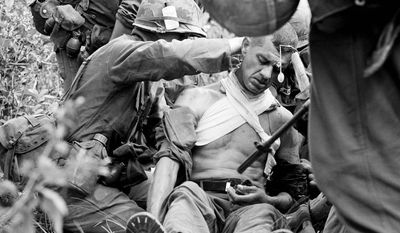 In this Jan. 16, 1966 file photo taken by Associated Press photographer Horst Faas, Lt. Col. George Eyster of Florida is placed on a stretcher after being shot by a Viet Cong sniper at Trung Lap, South Vietnam. (AP Photo/Horst Faas, File)