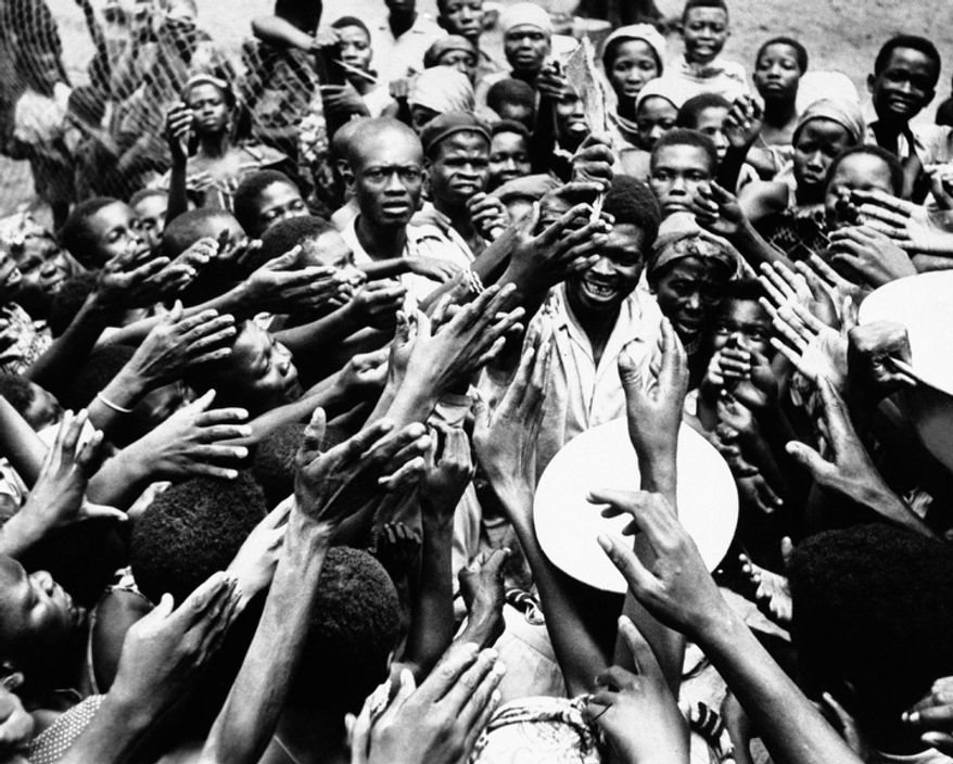 In this Jan. 26, 1961 file photo, scores of eager hands reach towards the Congolese official who distributes small rations of dried fish and palm oil to people at the hospital in Miabi, South Kasai, Congo.  (AP Photo/Horst Faas, File)
