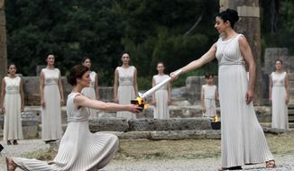 Actress Ino Menegaki (right), portraying a high priestess, passes on the Olympic flame she has just lit to a priestess holding a cauldron during the traditional flame-lighting ceremony on Thursday, May 10, 2012, in Ancient Olympia, Greece. The flame will travel to London, where the Summer Games will take place from July 27 to Aug. 12. (AP Photo/Petros Giannakouris)