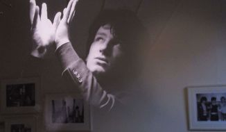 "With other photos reflected behind, a February 1979 photo of an 18-year-old Bono posing under a fluorescent light is one of the more striking images from the ""U2 1978-1981'"" exhibition opening in Dublin, Ireland, on Thursday, May 10, 2012. (AP Photo/Shawn Pogatchnik)"